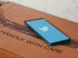 "Phone screen showing twitter logo placed on cardboard box labeled as ""Handle with care"""