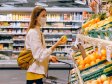 Woman wearing mask in grocery store and selecting produce. She is holding a lemon